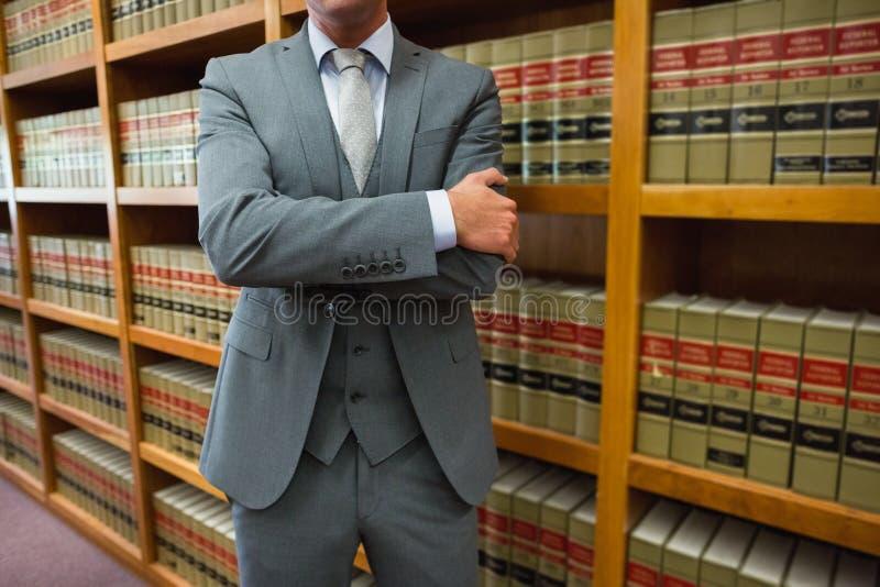 Юрист стоя в библиотеке закона стоковая фотография