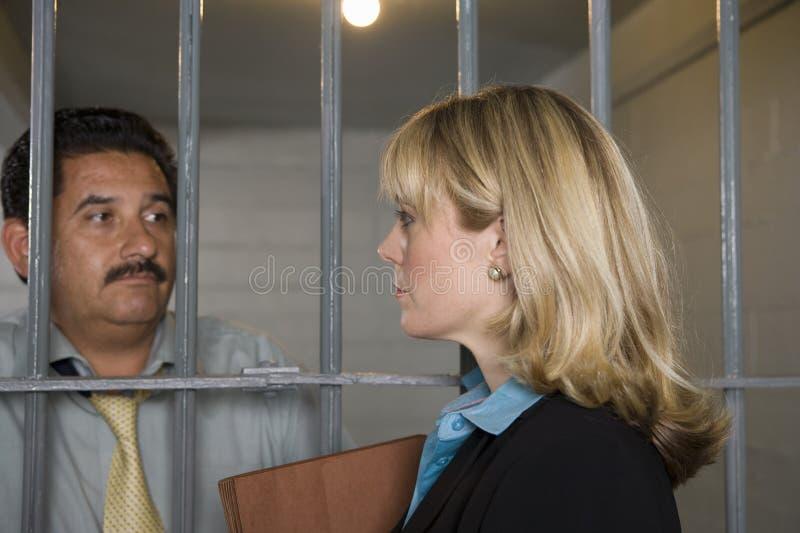 Юрист с преступником за решеткой стоковое фото