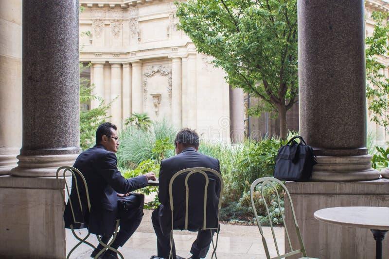 2 люд в деловых костюмах совещаются на таблице кафа в courtyar стоковые изображения rf
