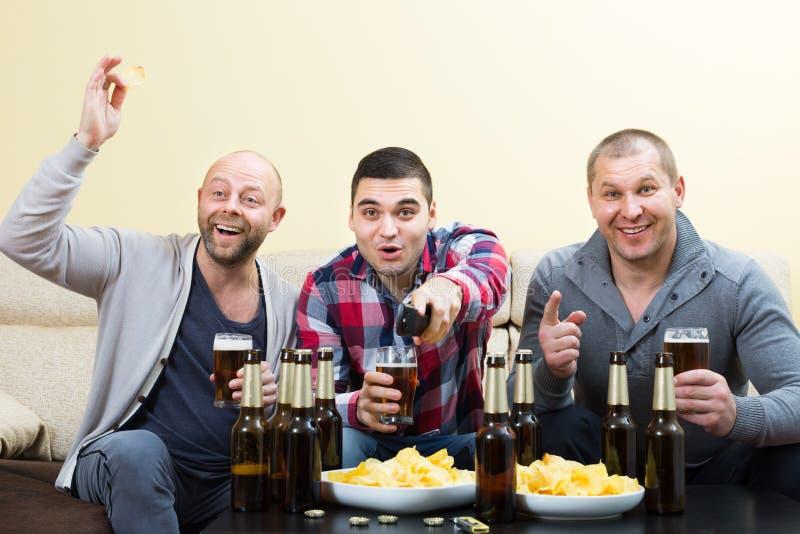 3 люд наблюдая футбол с пивом крытым стоковое фото