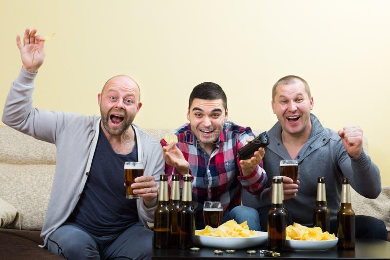 3 люд наблюдая футбол с пивом крытым стоковые фото