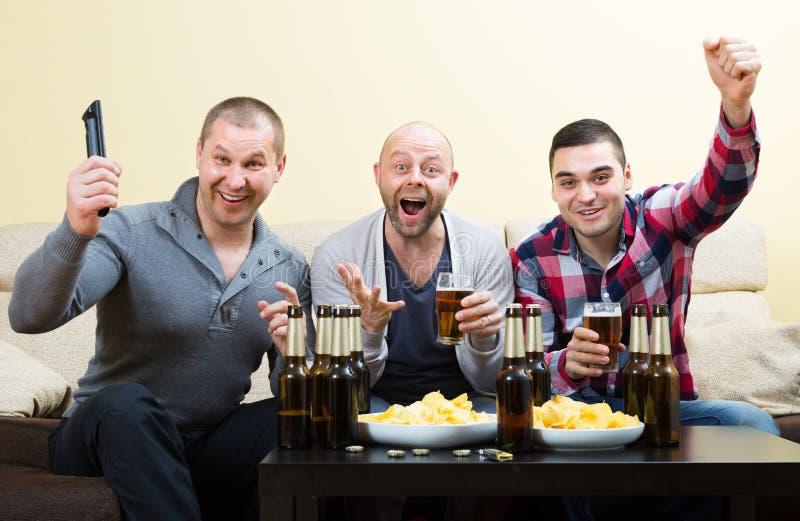 3 люд наблюдая футбол с пивом крытым стоковые фотографии rf