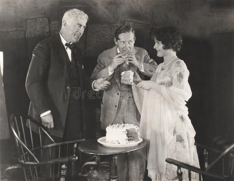 3 люд наслаждаясь куском торта стоковое изображение