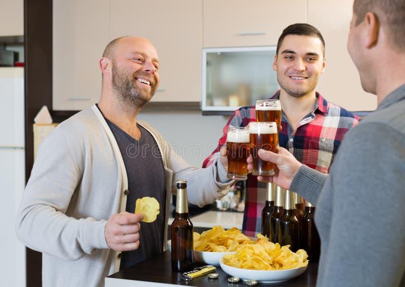3 люд с пивом на кухне стоковая фотография