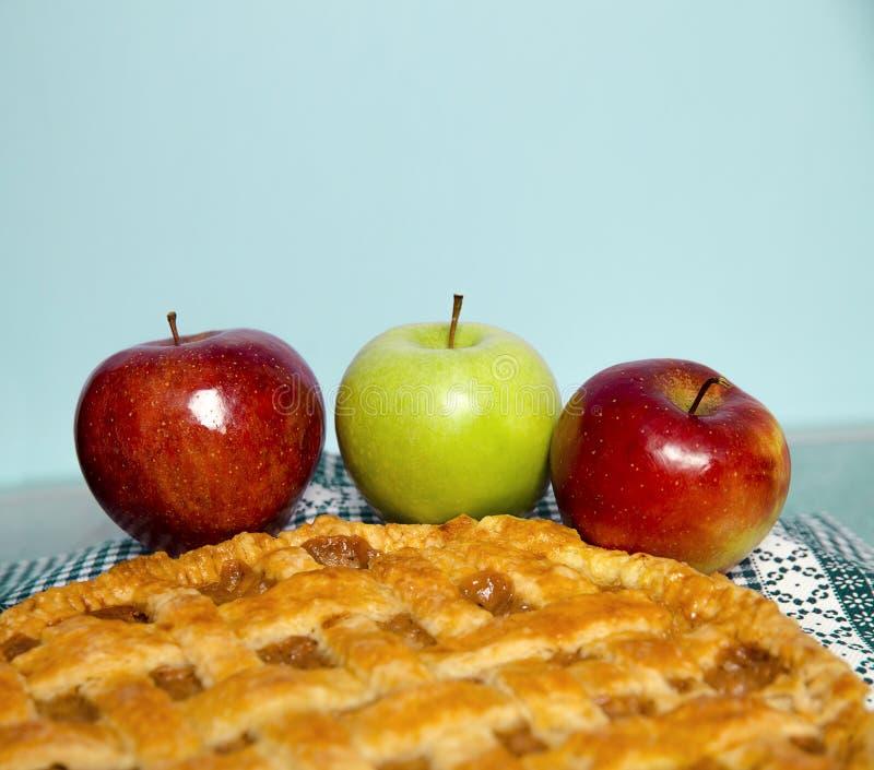 3 яблока рядом с свеже сделанным яблочным пирогом; стоковое изображение