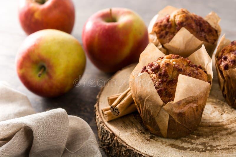 Яблоки и булочки циннамона на древесине стоковое изображение