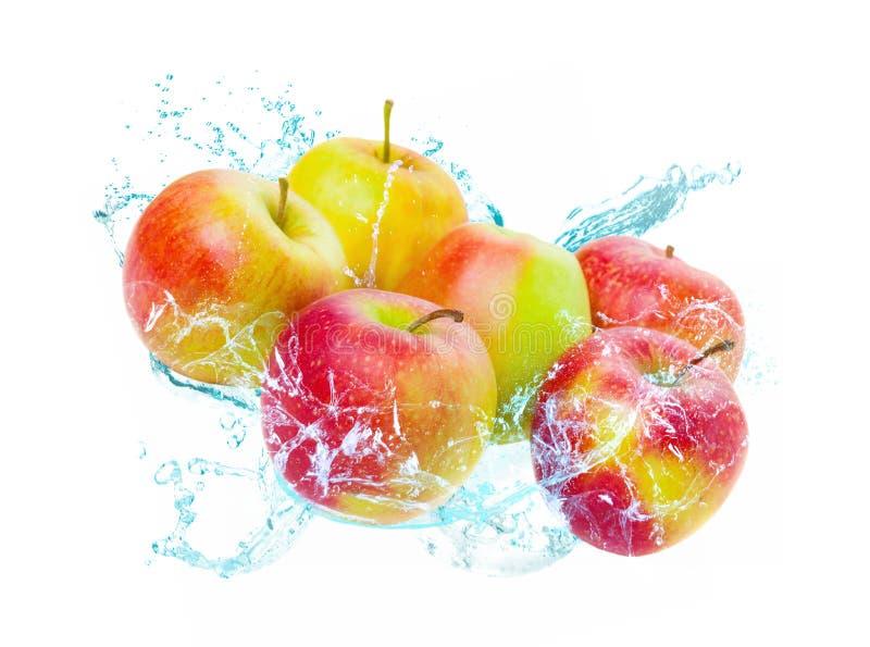 Яблоки падают в воду, изолированный выплеск воды стоковая фотография
