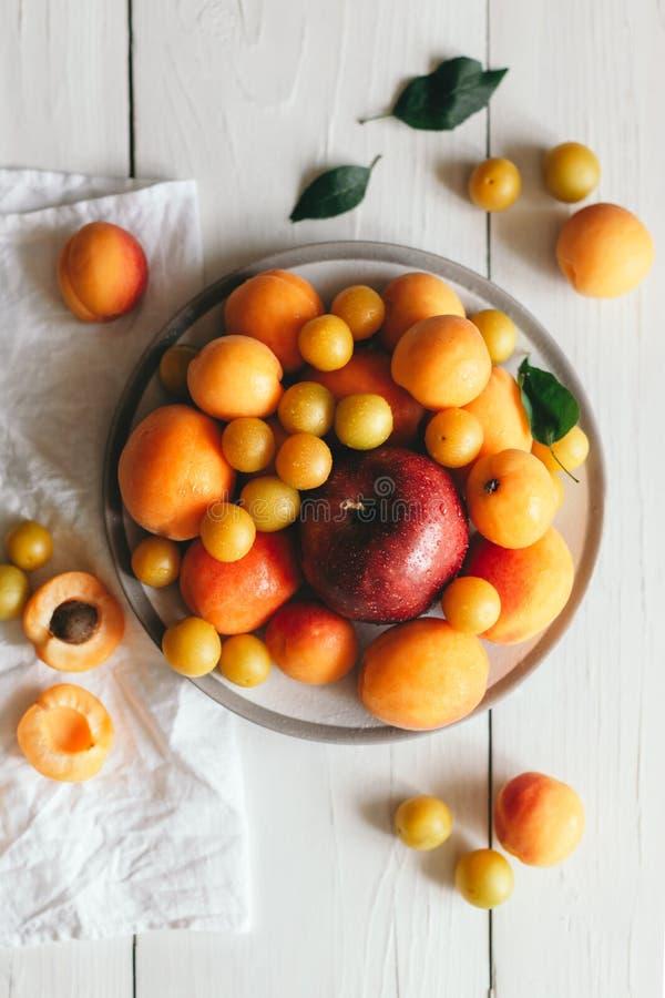Яблоко, абрикосы и вишн-сливы на белой плите стоковая фотография