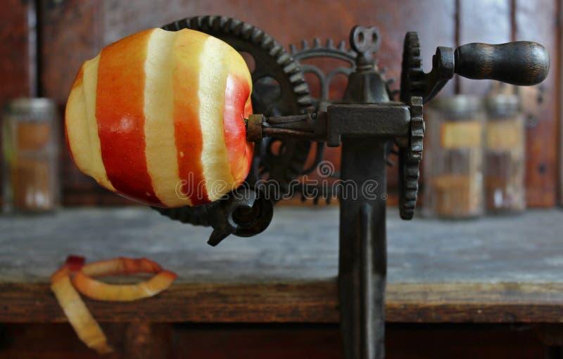 Яблоко будучи слезанным с винтажным Peeler с шестернями стоковое изображение rf