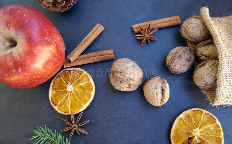 Яблоко, высушенные оранжевые куски, ручки циннамона, грецкие орехи и рождественская елка стоковые фотографии rf