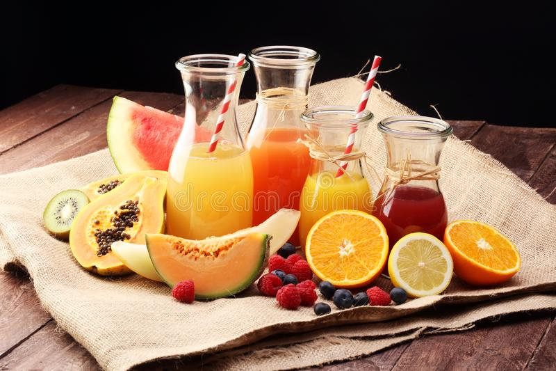 Яблоко и апельсиновый сок - несколько бутылок с соками плодоовощ и ягоды, винтажной деревянной предпосылкой, селективным фокусом стоковые фото