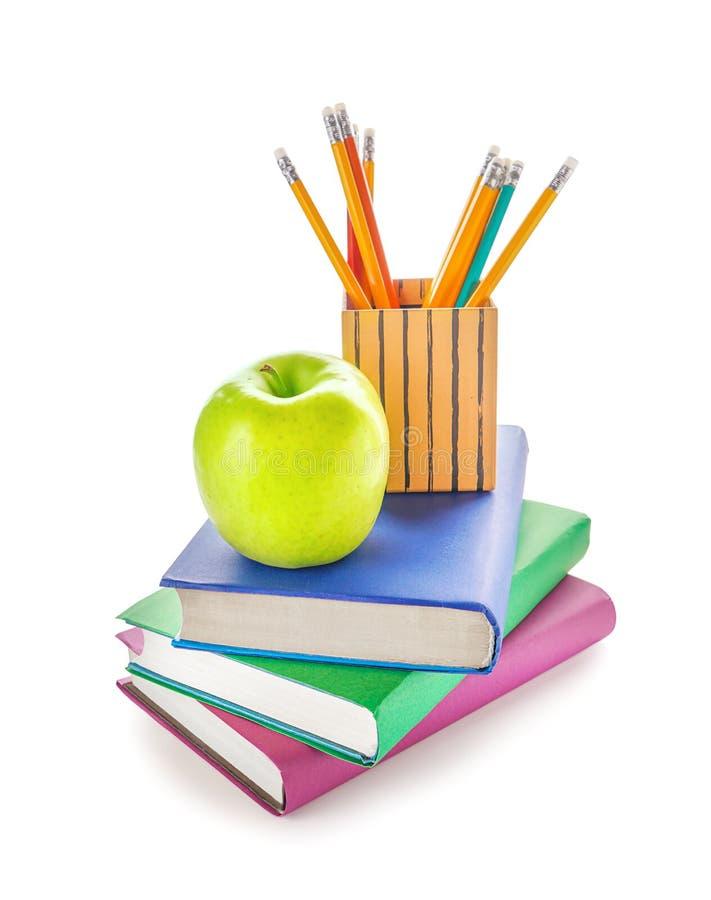 Яблоко и канцелярские принадлежности школы на белой предпосылке стоковая фотография rf