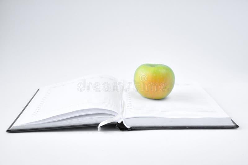 Яблоко на блокноте стоковые фотографии rf
