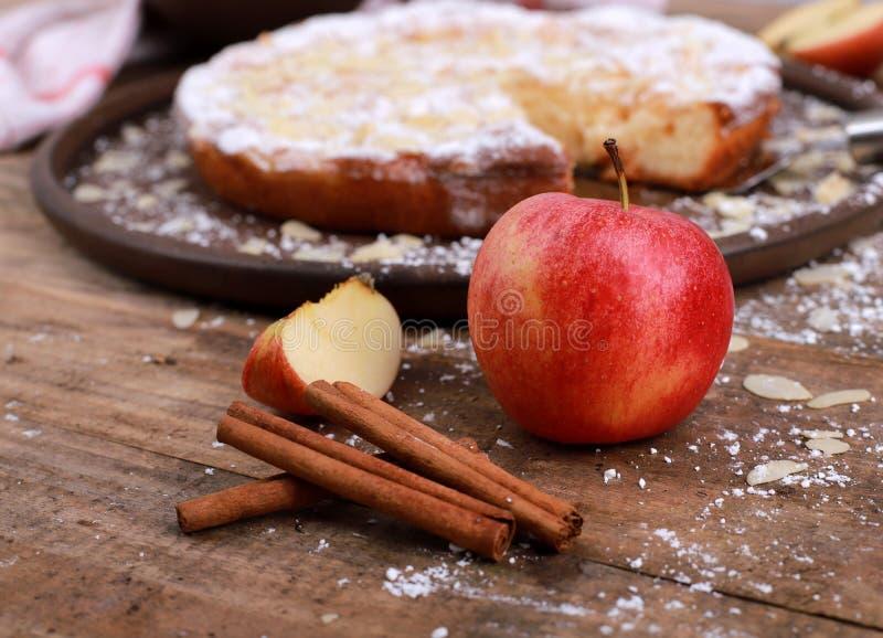 яблочный пирог - свежие яблоки и кориные палочки перед самодельным яблочным пирогом на деревенском деревянном столе стоковое фото