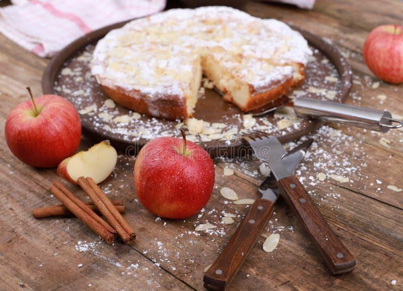 яблочный пирог - свежие яблоки и кориные палочки перед самодельным яблочным пирогом на деревенском деревянном столе стоковые изображения