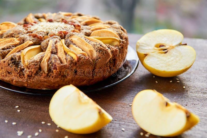 Яблочный пирог с айвой, маковыми семененами, изюминками и сезамом на темной плите украшенной с отрезанными свежими яблоками на де стоковое фото