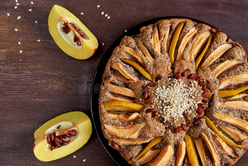 Яблочный пирог с айвой, маковыми семененами, изюминками и сезамом на темной плите Пирог украшенный с отрезанной свежей айвой стоковые фото