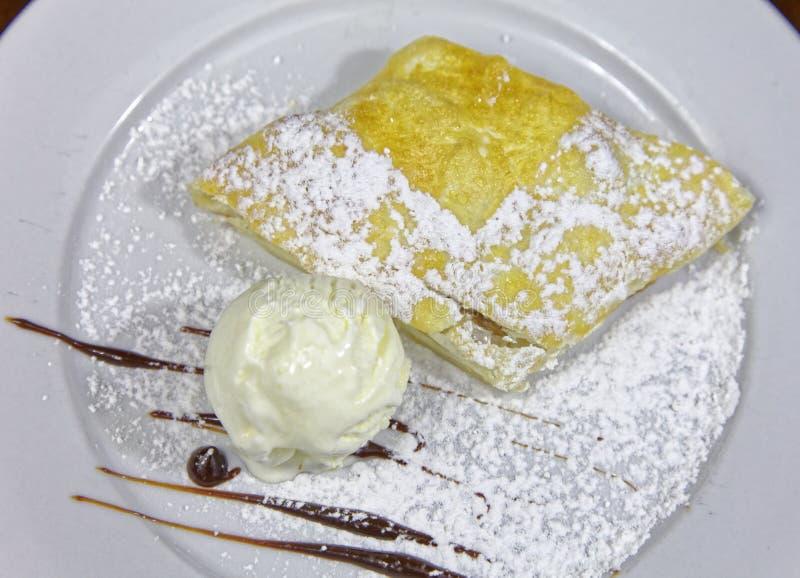 Яблочный пирог с мороженым на белой плите стоковая фотография