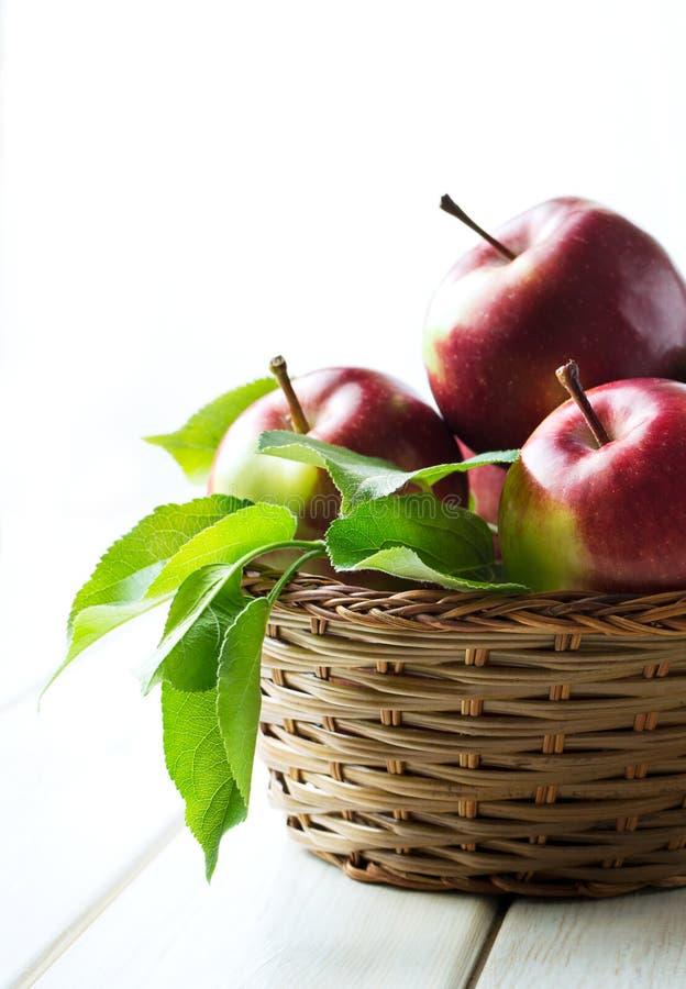 Яблоки в конце плетеной корзины вверх стоковое фото