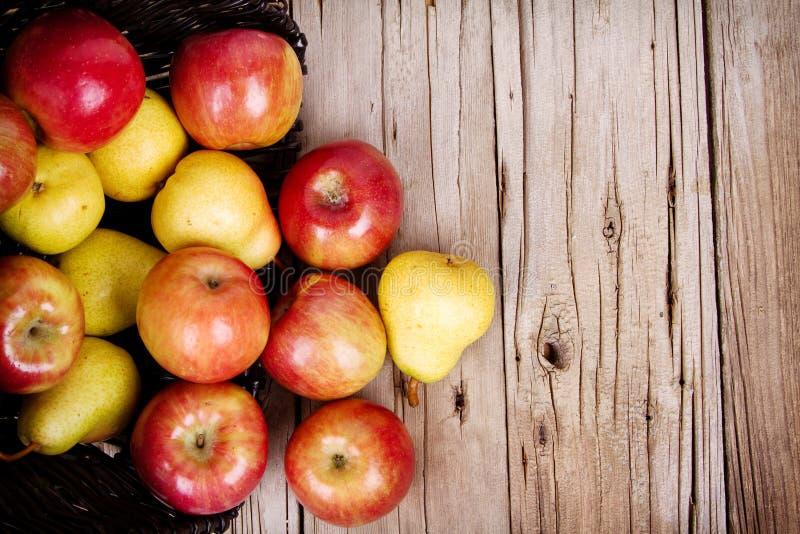 Яблоки и груши разливая из корзины стоковое изображение rf