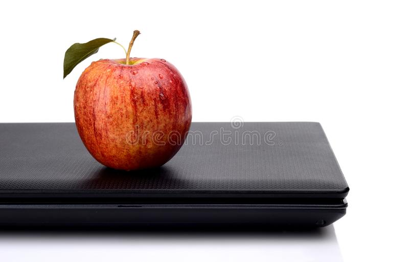 Яблоко закуски все красное с соком на компьтер-книжке стоковое фото