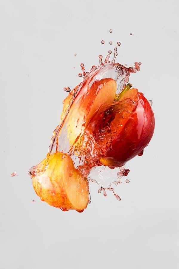 Яблоко и красный выплеск сока стоковая фотография rf