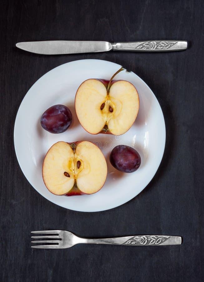 Яблоко и слива на белой плите с ножом и вилка на темной предпосылке стоковое изображение