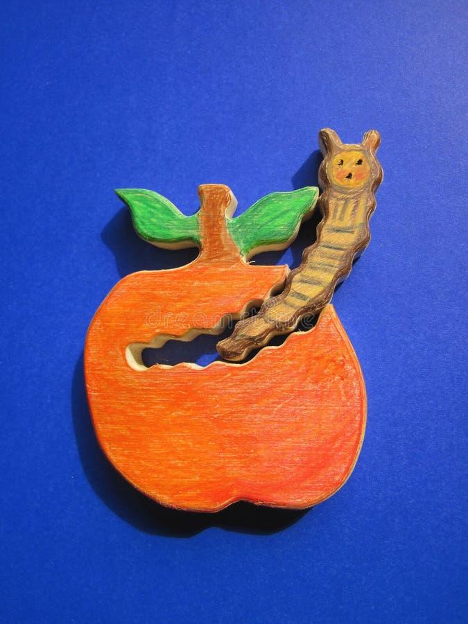 Яблоко и червь, деревянный высекать стоковая фотография rf