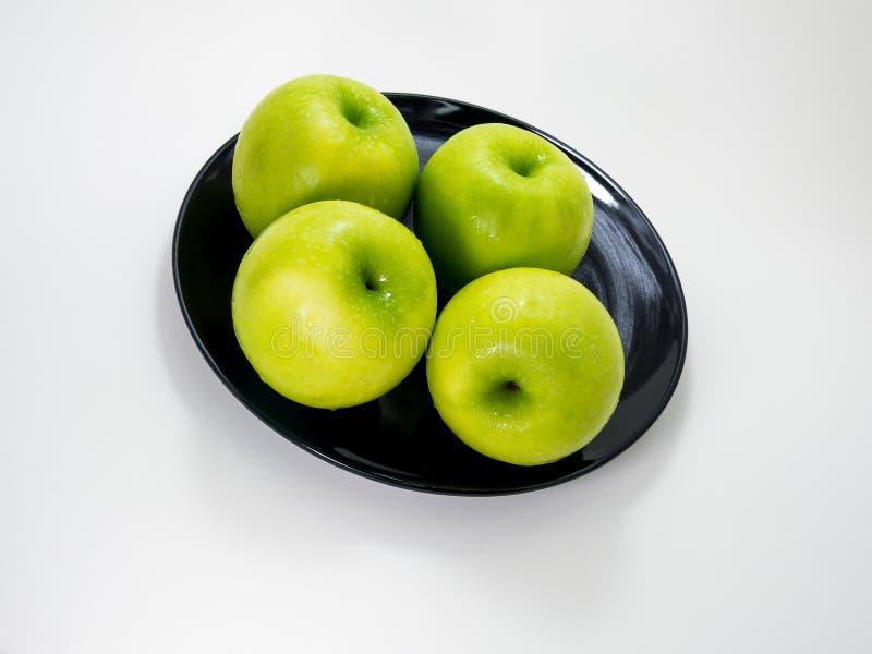 Яблоко и черное блюдо стоковое изображение