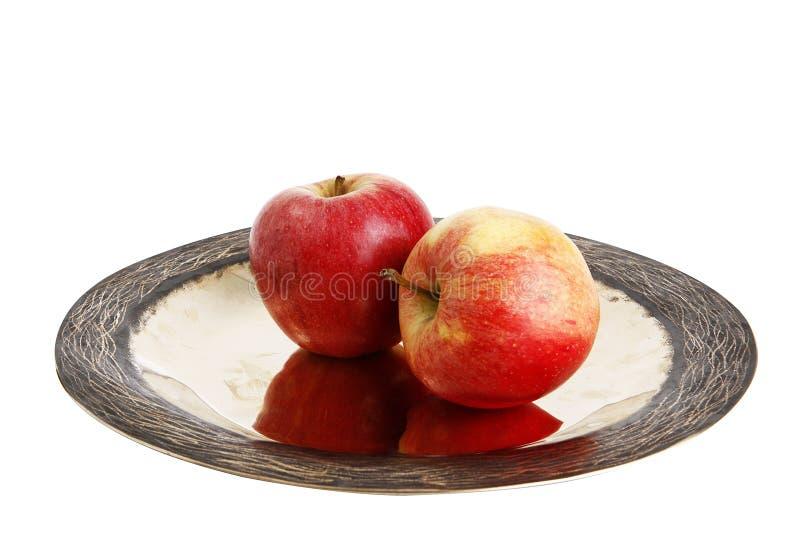 Яблоко 2 красных цветов на плите стоковые фото