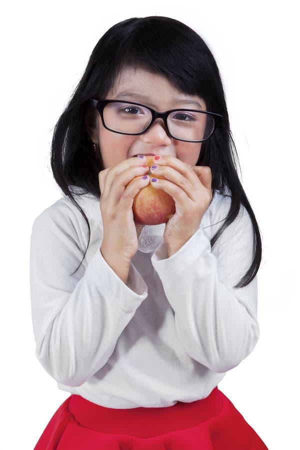 Яблоко маленькой девочки сдерживая в студии стоковое фото rf