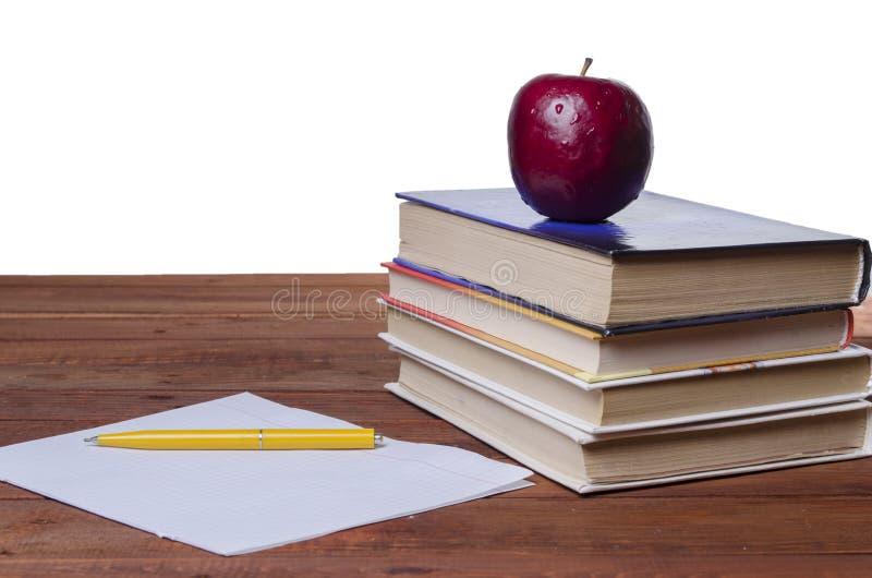 Яблоко на учебнике стоковое фото