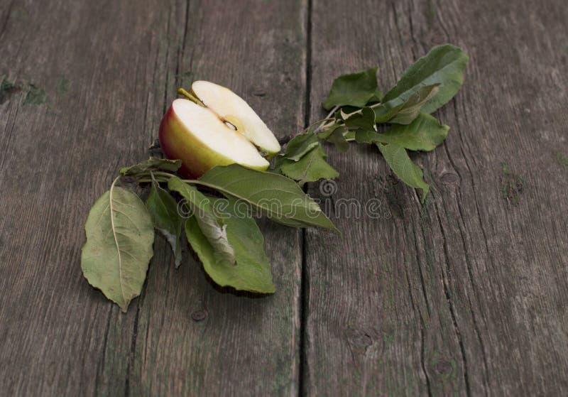 Яблоко отрезка с листьями на старом деревянном столе стоковые фотографии rf