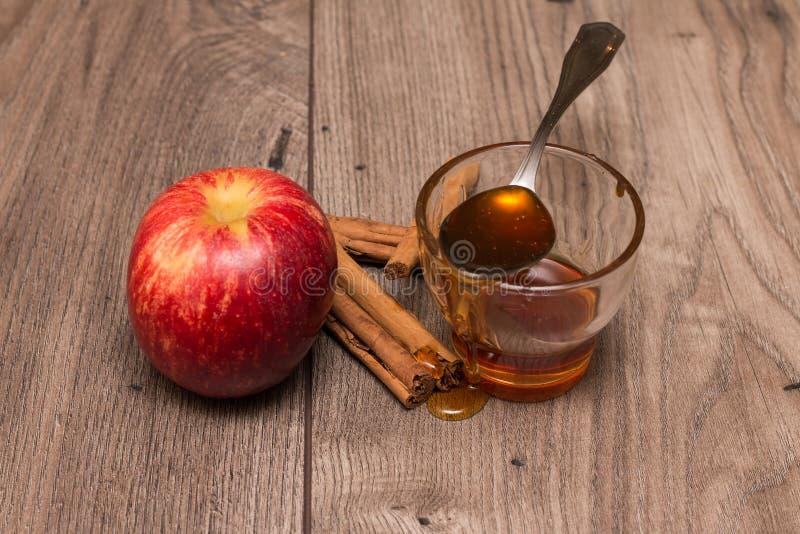 Яблоко, ручки циннамона, и стекло с медом стоковое изображение rf