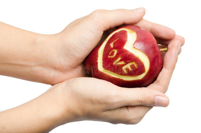 Яблоко, сердце, влюбленность в изоляте руки женщины на белой предпосылке стоковые изображения rf