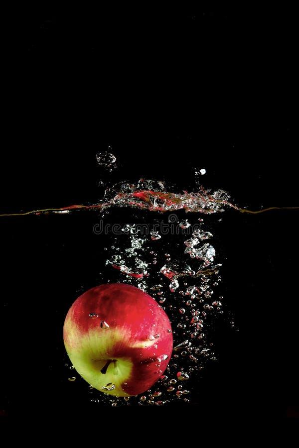 Яблоко Ed упало в воду стоковая фотография rf