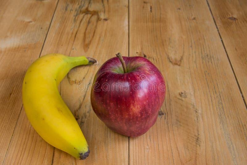 Яблоко nad банана на древесине стоковое изображение
