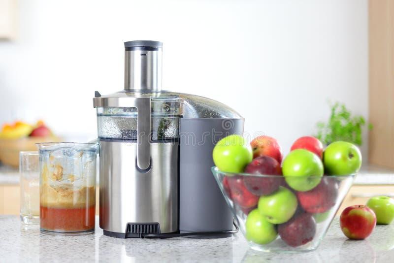 Яблочный сок на машине juicer - juicing стоковая фотография rf