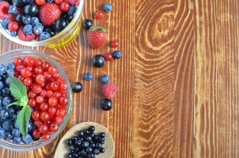 Ягоды красно-голубого цвета на еде деревянной предпосылки темного коричневого цвета здоровой стоковое фото