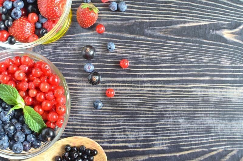 Ягоды красны и голубы в стеклянном шаре на черной деревянной предпосылке стоковое фото