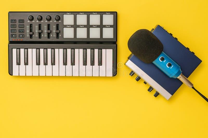 Ядровая карта, смеситель музыки и микрофон на желтой предпосылке Концепция организации рабочего места стоковые фото