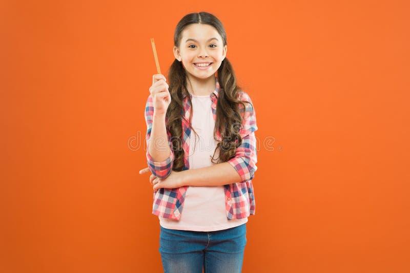 Язык исследования Ребенок делая домашнюю работу Ручка владением девушки Девушка милая имеющ свежую идею Напишите эссе или примеча стоковая фотография