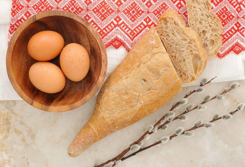 Яичка в деревянных плите, пита хлеба и хворостинах вербы стоковое изображение