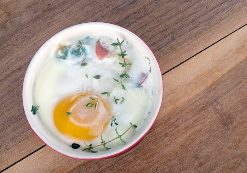 Яичка испекли с сметанообразными соусом, грибами, ветчиной, сыром и травами i стоковые фотографии rf