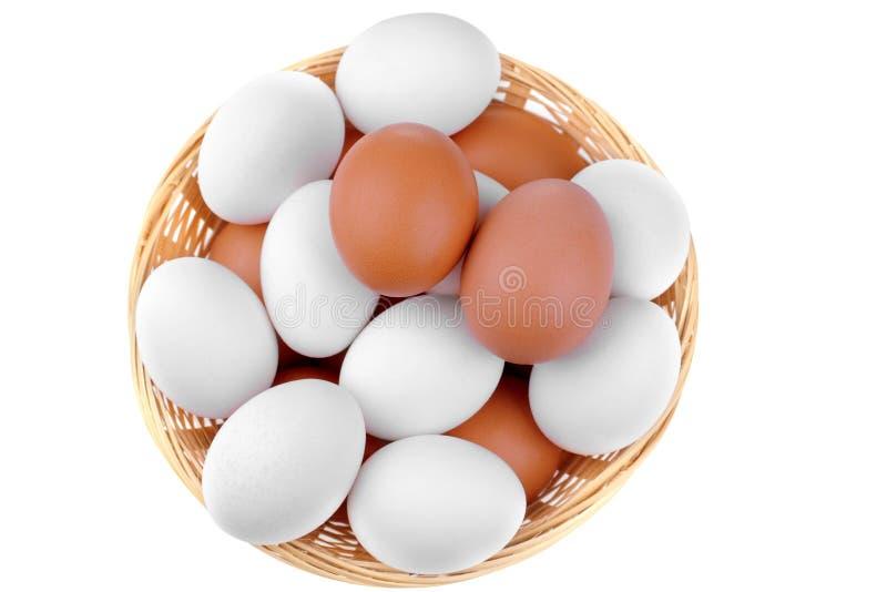 Яичка много цыпленка коричневые и белые в плетеной корзине на белой предпосылке изолировано стоковые изображения