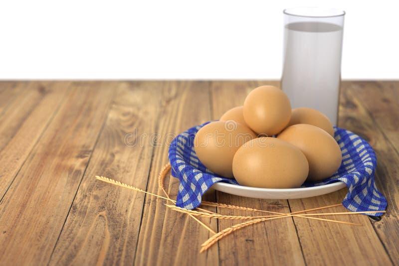Яичка на голубом полотенце в керамическом шаре на деревянном столе с стеклом молока белизна изолированная предпосылкой иллюстрация штока