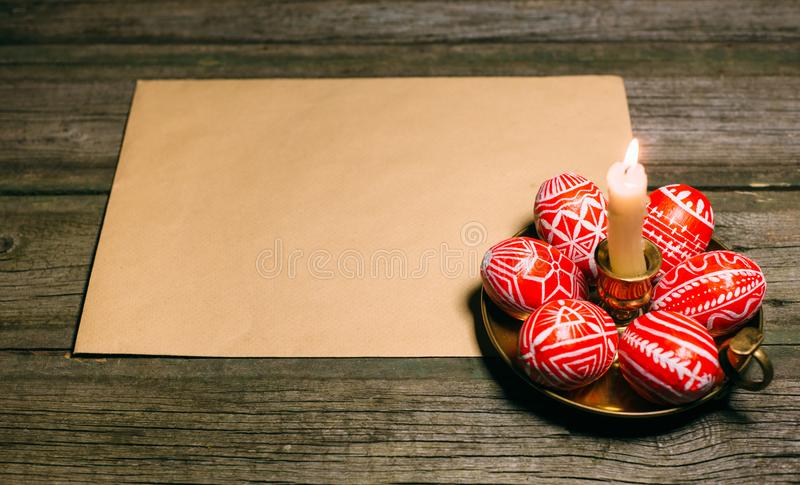 Яичка пасхи красные с фольклорной белой картиной кладут вокруг на латунный подсвечник около бумаги на деревенской деревянной доск стоковое изображение rf