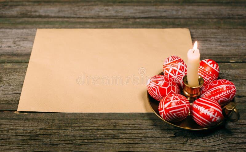 Яичка пасхи красные с фольклорной белой картиной кладут вокруг на латунный подсвечник около бумаги на деревенской деревянной табл стоковое изображение rf