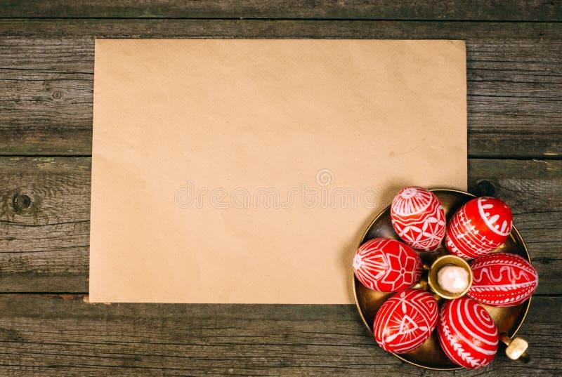 Яичка пасхи крупного плана красные с фольклорной белой картиной кладут вокруг на латунный подсвечник около бумаги на деревенской  стоковые изображения rf