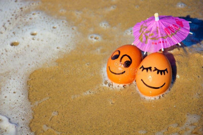 Яичка пасхи смешные под зонтиком на пляже стоковые изображения